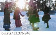 Russian folk - men and women in Russian folk costumes are dancing in pairs in a winter park. Стоковое видео, видеограф Константин Шишкин / Фотобанк Лори