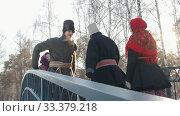 Russian folk - men in traditional costumes dance on the bridge. Стоковое видео, видеограф Константин Шишкин / Фотобанк Лори
