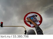 Купить «A radical student of the Universidad Nacional de Colombia attaches a poster to a traffic sign during a protest march against government's policies and...», фото № 33380798, снято 24 октября 2019 г. (c) age Fotostock / Фотобанк Лори