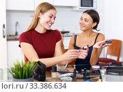 Купить «Two smiling young female friends looking cosmetics before make-up at table», фото № 33386634, снято 29 августа 2018 г. (c) Яков Филимонов / Фотобанк Лори