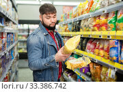 Купить «Portrait of doubting bearded guy choosing potato chips at grocery store», фото № 33386742, снято 17 февраля 2020 г. (c) Яков Филимонов / Фотобанк Лори
