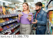 Happy young couple looking for sweet chocolate in grocery store. Стоковое фото, фотограф Яков Филимонов / Фотобанк Лори