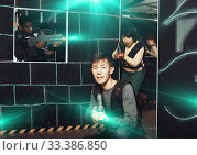Купить «Emotional Asian man with laser pistol playing laser tag with fri», фото № 33386850, снято 23 января 2019 г. (c) Яков Филимонов / Фотобанк Лори