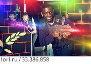 Купить «Portrait of cheerful African-American with laser gun having fun», фото № 33386858, снято 23 января 2019 г. (c) Яков Филимонов / Фотобанк Лори