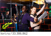 couple standing back to back holding laser guns during lasertag game. Стоковое фото, фотограф Яков Филимонов / Фотобанк Лори