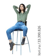 Купить «A young woman in jeans, boots and a khaki shirt is sitting on a high chair. Isolated on white.», фото № 33390826, снято 11 января 2020 г. (c) Serg Zastavkin / Фотобанк Лори