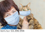 Portrait of a woman with a cat on her hands in a medical mask. Стоковое фото, фотограф Акиньшин Владимир / Фотобанк Лори