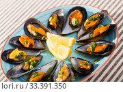 Купить «Baked mussels with lemon slices on color plate», фото № 33391350, снято 25 июня 2018 г. (c) Яков Филимонов / Фотобанк Лори