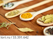 Купить «spoons with different spices on wooden table», фото № 33391642, снято 6 сентября 2018 г. (c) Syda Productions / Фотобанк Лори