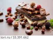 Купить «close up of different chocolates, candies and nuts», фото № 33391662, снято 1 февраля 2019 г. (c) Syda Productions / Фотобанк Лори