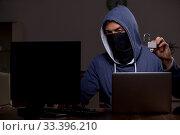 Купить «Male hacker hacking security firewall late in office», фото № 33396210, снято 15 мая 2019 г. (c) Elnur / Фотобанк Лори