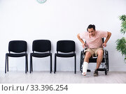 Купить «Young injured man waiting for his turn in hospital hall», фото № 33396254, снято 3 мая 2019 г. (c) Elnur / Фотобанк Лори