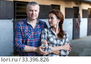 Купить «Positive family couple with belly-band standing at stable outdoor», фото № 33396826, снято 4 июля 2018 г. (c) Яков Филимонов / Фотобанк Лори