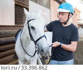 Mature smiling man farmer in helmet standing with white horse at stable. Стоковое фото, фотограф Яков Филимонов / Фотобанк Лори