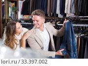 Купить «Adult loving couple deciding on new trousers», фото № 33397002, снято 4 апреля 2020 г. (c) Яков Филимонов / Фотобанк Лори