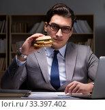 Купить «Businessman late at night eating a burger», фото № 33397402, снято 30 января 2017 г. (c) Elnur / Фотобанк Лори