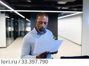 Купить «African American man reading papers in office », фото № 33397790, снято 12 октября 2019 г. (c) Wavebreak Media / Фотобанк Лори