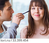 Купить «Man doing make-up for cute woman in beauty salon», фото № 33399454, снято 18 декабря 2017 г. (c) Elnur / Фотобанк Лори