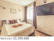 Купить «Fresh clean comfy bed in bedroom with tv», фото № 33399686, снято 5 июля 2020 г. (c) Ольга Сапегина / Фотобанк Лори