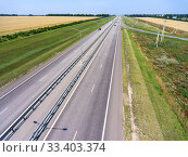 Купить «Wide highway with four lanes, aerial view at straight motorway in agricultural fields. Russia», фото № 33403374, снято 30 июля 2018 г. (c) Кекяляйнен Андрей / Фотобанк Лори