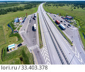 Wide straight toll highway M-11 is passing in forest. View from above. The Moscow-Saint Petersburg motorway is designed as the M11 Neva (2018 год). Редакционное фото, фотограф Кекяляйнен Андрей / Фотобанк Лори