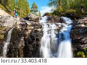 Купить «Man end woman hikers standing next to beautiful waterfall in Khibiny mountains. The Kola peninsula, Russia», фото № 33403418, снято 18 июля 2015 г. (c) Кекяляйнен Андрей / Фотобанк Лори