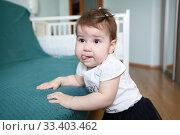 Portrait of little girl putting tongue out, holding on to the sofa in domestic room. Стоковое фото, фотограф Кекяляйнен Андрей / Фотобанк Лори