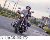 Woman motorcyclist riding on her chopper motorcycle on road. Стоковое фото, фотограф Кекяляйнен Андрей / Фотобанк Лори