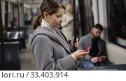 Купить «Positive woman reading from mobile phone screen in metro», видеоролик № 33403914, снято 11 ноября 2019 г. (c) Яков Филимонов / Фотобанк Лори