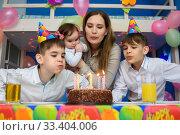 Семья дуют на свечки на пироге в честь дня рождения. Стоковое фото, фотограф Иванов Алексей / Фотобанк Лори