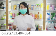 Купить «Chinese woman pharmacist in protective facial mask keeps track of drugs in interior of pharmacy», видеоролик № 33404034, снято 8 июля 2020 г. (c) Яков Филимонов / Фотобанк Лори