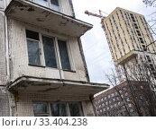 Балкон готовой к сносу пятиэтажки на фоне строящейся жилой высотки. Редакционное фото, фотограф Сайганов Александр / Фотобанк Лори