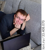 Купить «Smiling young man works on sofa at home during coronavirus pandemic», фото № 33408070, снято 21 марта 2020 г. (c) Валерия Попова / Фотобанк Лори