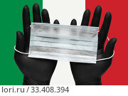 Купить «Doctor holds face mask in hands in black medical gloves on background colors flag of Italy or Italian Tricolour. Pandemic insurance coronavirus», фото № 33408394, снято 6 марта 2020 г. (c) А. А. Пирагис / Фотобанк Лори
