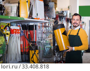 professional male seller showing assortment in garden equipment shop. Стоковое фото, фотограф Яков Филимонов / Фотобанк Лори