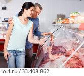 Купить «Glad couple choosing meat and discussing», фото № 33408862, снято 22 июня 2018 г. (c) Яков Филимонов / Фотобанк Лори
