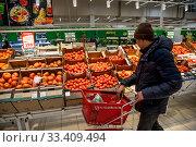 Покупатель выбирает помидоры в овощном отделе гипермаркета АШАН в торговом центре Мега в Химках, Московская область, Россия. Редакционное фото, фотограф Николай Винокуров / Фотобанк Лори