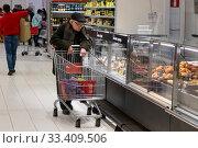 Покупатель в магазине гипермаркете АШАН в торговом центре Мега в Химках, Россия (2020 год). Редакционное фото, фотограф Николай Винокуров / Фотобанк Лори
