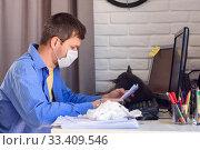 Купить «Мужчина в медицинской маске читает документ, работая удаленно», фото № 33409546, снято 22 марта 2020 г. (c) Иванов Алексей / Фотобанк Лори