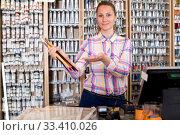 Купить «Female seller posing at counter», фото № 33410026, снято 12 апреля 2017 г. (c) Яков Филимонов / Фотобанк Лори