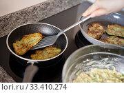Купить «Process frying zucchini pancakes in frying pan in kitchen», фото № 33410274, снято 7 апреля 2020 г. (c) Яков Филимонов / Фотобанк Лори