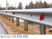 Купить «Retro-reflecting optical units are on a metal guardrail», фото № 33410458, снято 9 ноября 2019 г. (c) EugeneSergeev / Фотобанк Лори