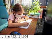 Girl schoolgirl in a medical mask does school homework at home in front of a computer. Стоковое фото, фотограф Екатерина Кузнецова / Фотобанк Лори