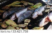 Купить «Cooking sea bass fish with vegetables on a grill barbecue», видеоролик № 33421758, снято 21 марта 2020 г. (c) Serg Zastavkin / Фотобанк Лори