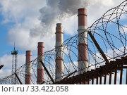 Купить «Smoke from factory pipes behind a fence with barbed wire», фото № 33422058, снято 22 марта 2020 г. (c) Алексей Кузнецов / Фотобанк Лори