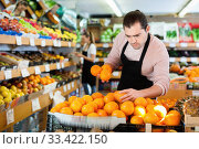 Купить «Young man in apron selling fresh oranges and fruits on the supermarket», фото № 33422150, снято 27 апреля 2019 г. (c) Яков Филимонов / Фотобанк Лори