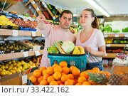 Купить «Family couple standing with full cart after shopping and pointing to shelves», фото № 33422162, снято 27 апреля 2019 г. (c) Яков Филимонов / Фотобанк Лори