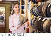 Купить «Saleswoman arranging caps on racks in store», фото № 33422214, снято 17 декабря 2019 г. (c) Яков Филимонов / Фотобанк Лори