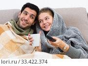 Loving couple snuggling on sofa watching TV. Стоковое фото, фотограф Яков Филимонов / Фотобанк Лори