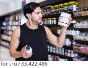 Купить «Young muscular sportman choosing sport dietary supplements», фото № 33422486, снято 28 марта 2018 г. (c) Яков Филимонов / Фотобанк Лори